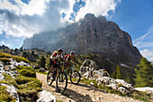 Mountain biker couple at the Ciampinoi, behind it Langkofel, Trentino South Tyrol, Italy