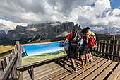 Mountain bikers in the Langkofel area standing at a panorama board, behind it Sella group, Trentino South Tyrol, Italy