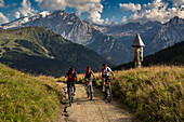 Mountain biker at Col Rodella, behind it Marmolada group, Trentino South Tyrol, Italy