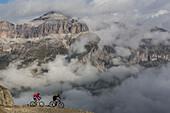 Mountain bikers near Porta Vescovo in frot of the Sellagruppe, Belluno, Veneto, Italy