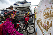 Mountain bikers looking at an environment map at the mountain station Col Alt, Corvara, Trentino South Tyrol, Italy