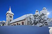 Rays of winter sun illuminate the snowy landscape and the typical church, Maloja, Engadine, Graubunden Grisons Canton, Switzerland, Europe