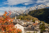 Autumn colors frame the village of Ardez surrounded by woods and snowy peaks, Engadine, Canton of Graubunden, Switzerland, Europe