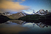 The stars illuminate the snowy peaks and reflected in Lac de Cheserys, Chamonix, Haute Savoie, French Alps, France, Europe