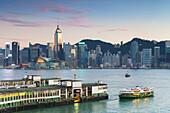 View of Star Ferry Terminal and Hong Kong Island skyline at dusk, Hong Kong, China, Asia