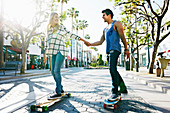 Caucasian couple riding skateboards