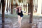 Caucasian woman splashing in ocean under boardwalk