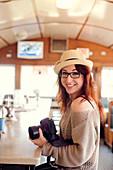 Caucasian woman holding camera in restaurant