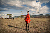 Black boy in traditional clothing standing in remote field