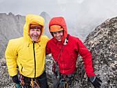 Caucasian climbers smiling on hillside