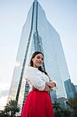 Hispanic businesswoman standing near highrise