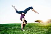 Asian woman practicing yoga outdoors