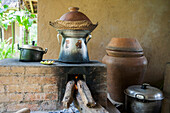 Pots cooking food over wood stove in outdoor kitchen