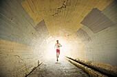 Caucasian man jogging in tunnel