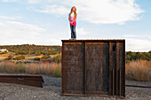 Caucasian girl standing on rusting structure outdoors