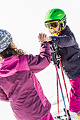 girl and boy giving a high five whilst skiing, Pfronten, Allgaeu, Bavaria, Germany
