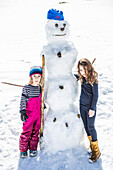girl and boy building a snowman in winter, Pfronten, Allgaeu, Bavaria, Germany