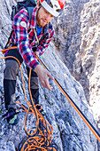 Climber pulling ropes up on the Herzogkante, Laliderer Northface, Lalidererspitze, Hinterriss, Ahornboden, Karwendel, Bavaria, Germany