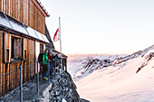 Group standing in front of the Oberaarjoch hut at sunrise, Wallis, Switzerland