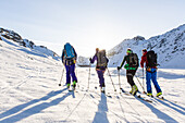 Group of people on a ski tour over the Oberaarjoch lake at morning light, Grimselpass, Wallis, Switzerland