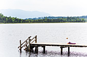 woman is making yoga on the boardwalk, sun salute, Kirchsee, Bad Toelz, Bavaria, Germany