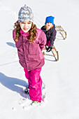 Girl pulling boy on their sleds, Pfronten, Allgaeu, Bavaria, Germany