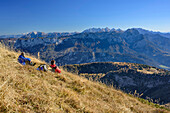 Two persons sitting at Sonntagshorn and looking towards Berchtesgaden Alps, Sonntagshorn, Chiemgau Alps, Salzburg, Austria