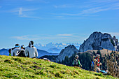 Several persons having a break at summit of Setzberg, High Tauern range and Plankenstein in background, Setzberg, Bavarian Alps, Upper Bavaria, Bavaria, Germany