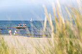 People on the jetty and swimming in the sea, beach in the north of the island, sailing boat, summer, Baltic sea, Bornholm, Sandvig, Denmark, Europe