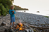 Boy, 5 years old, standing near the campfire, child, Adventure, Baltic sea, MR, Bornholm, near Gudhjem, Denmark, Europe