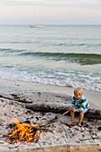 5 jähriger Junge sitzt am Lagerfeuer, Abenteuer, Abenteuerurlaub, Segelboot, Traumstrand zwischen Strandmarken und Dueodde, Sommer, dänische Ostseeinsel, Ostsee, Insel Bornholm, Strandmarken, Dänemark, Europa, MR