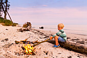 5 jähriger Junge sitzt am Lagerfeuer, Abenteuer, Abenteuerurlaub, Sonnenuntergang, Traumstrand zwischen Strandmarken und Dueodde, Sommer, dänische Ostseeinsel, Ostsee, Insel Bornholm, Strandmarken, Dänemark, Europa
