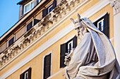 Statue of historical male figure and yellow building, Rome, Italy