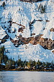 Snow covered cliffs and evergreen trees bathed in sunset light on the shore of Kings Bay, Prince William Sound, Whittier, Alaska, United States of America