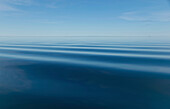 Surface of blue water with slight ripples and blue sky with horizon in the distance