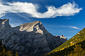 Close up of mountain peak lit by the sun in an alpine valley with autumn colours and an interesting cloud formation and blue sky, Kananaskis Provincial Park, Alberta, Canada