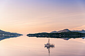 Scenic sunrise view of a small fishing boat reflecting in Ketchikan harbor, Southeast Alaska, Spring