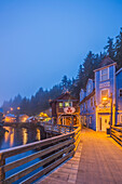 Tourist shops and homes along Creek Street in downtown Ketchikan on a foggy evening, Southeast Alaska, USA, Spring, HDR
