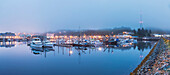 Panorama of boats in Ketchikan Harbor reflecting on the calm ocean waters on a foggy night, Ketchikan, Southeast Alaska