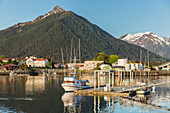 Fishing boat moored along the pier in Sitka Harbor and the mountains in the background, Southeast Alaska, USA, Summer