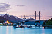 Fishing boat moored along the pier in Sitka Harbor with O'Connell Bridge and the mountains in the background at twilight, Southeast Alaska, USA, Summer