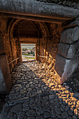 Interior of a building with arched roof, stone beams and cobblestone ground, Corinth, Greece