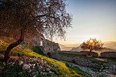 Ruins of stone wall and building at sunset, Corinth, Greece