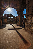 Sunburst through an archway at the Colosseum and a shadow of a cross, Rome, Italy