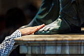 A woman's hand touches the foot of a statue, St. Peter's Basilica, Rome, Italy