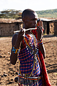A young Masai man dressed in a traditional costume of blue, black and red checked clothing pretends to play the flute with a stick in the middle of his village, Narok, Kenya
