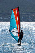 Windsurfing with sunlight reflected on the water and a view of the shoreline, Turkey