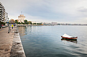 A lone boat moored in the water along the waterfront with White Tower in the distance, Thessaloniki, Greece