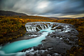 Long exposure of water flowing over rock in a stream and dark clouds in the sky, Bruarfoss, Iceland