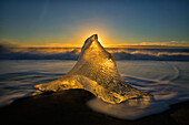 A peaked ice formation glowing golden in the sunlight, Iceland